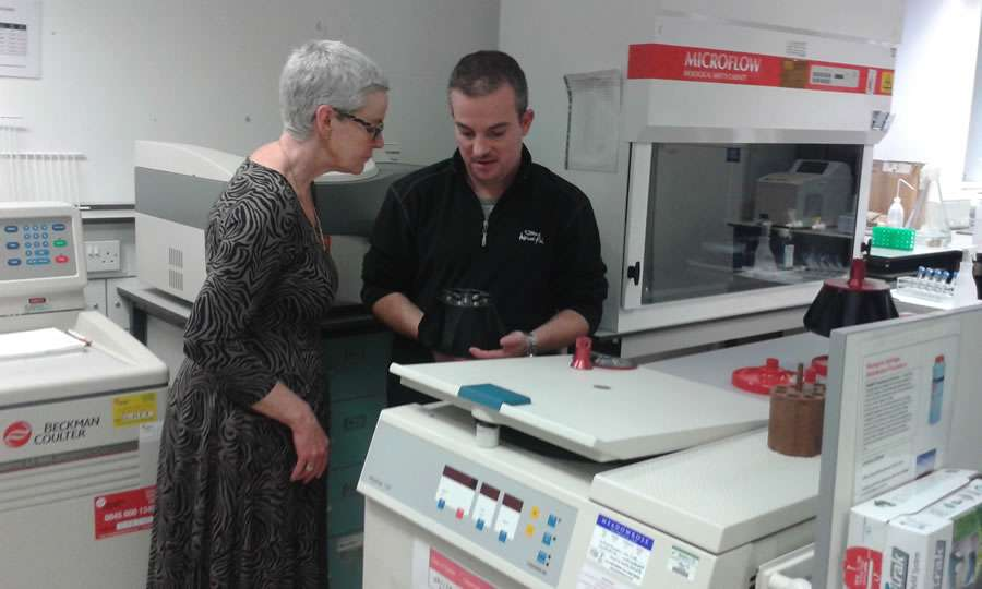 Toni Whitehead being shown the research equipment at Cancer Research Wales